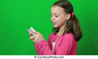 Little girl with smartphone in the hands laughing and...