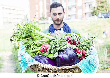young farmer showing a basket of vegetables in his garden