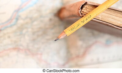 Travelling the World inscription on pencil, book and map