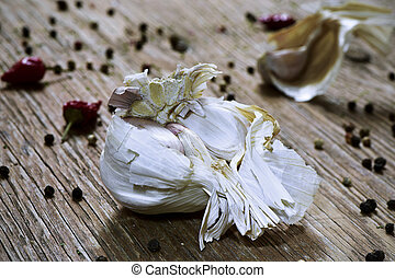 head of garlic on a wooden table - closeup of a head of...