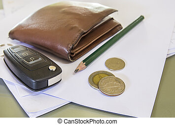 Black car key and money on a white paper. Focus on a key.