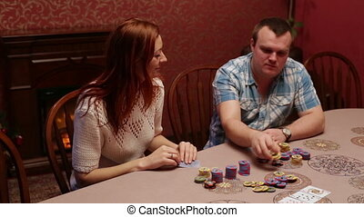 A woman with a man playing poker in the casino - People...