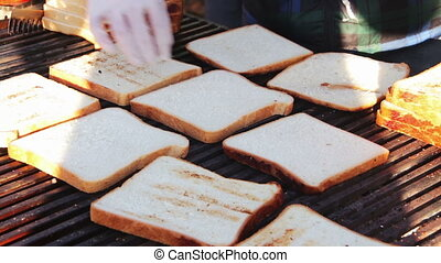 Bread for toast prepared on the grill - Cook standing in the...