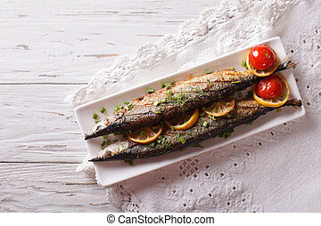 saury grilled with vegetables on a plate. Horizontal top...