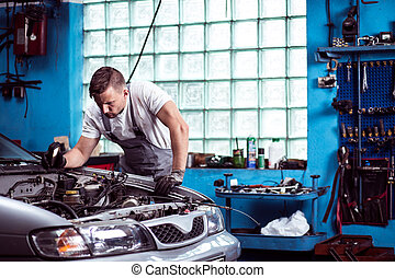 Car mechanic at work - Young strong car mechanic at work in...