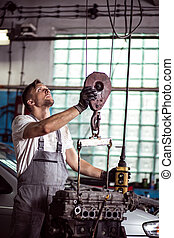 Mechanic and suspended engine - Young working mechanic and...