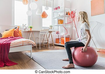 Girl sitting on fitness ball