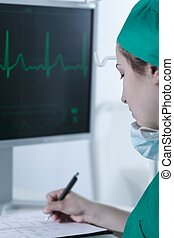 Doctor writing down electrocardiogram results