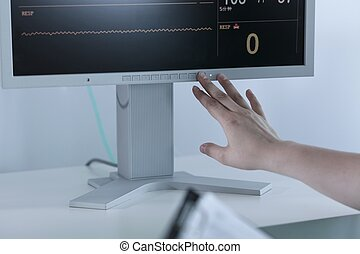 Nurse turning off electrocardiogram - Close-up on nurse...
