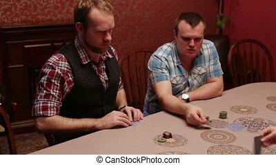 The men sitting at a table playing poker - People playing...