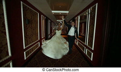 Newlyweds in a Hotel - dynamically couple walking down the...
