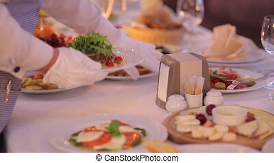 Waiter Serves Banquet Table - the waiter puts a plate of...