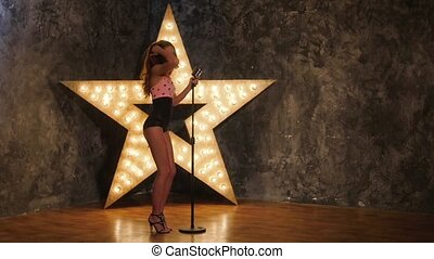 sexy woman singer with microphone, dances shining star in...