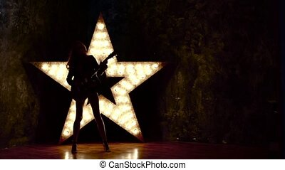 sexy rock girl playing the electric guitar, shining star in...