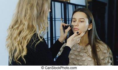 makeup artist applies makeup young girl