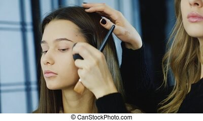 Young woman does make-up girlfriend
