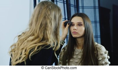 Makeup artist corrects make-up of a young girl