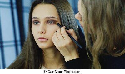 Beautiful young woman apply makeup