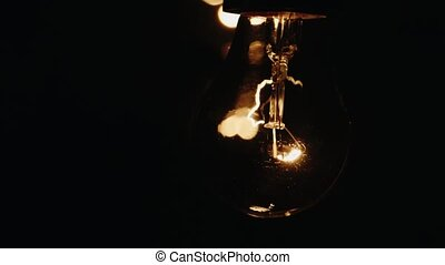 Light bulb lit brightly against a black background