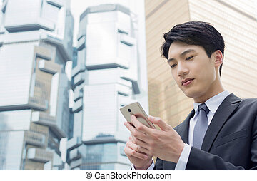 Asian businessman using cellphone - Confident young Asian...