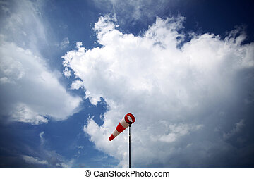 Wind vane - A red wind vane against a blue cloudy sky