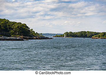 Summer on Casco Bay - Sailboat wends its way past islands on...