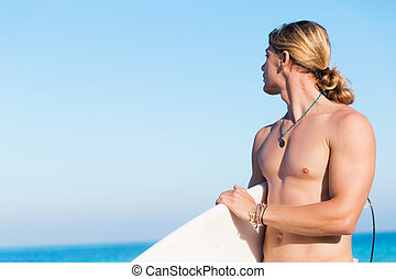 Ready to hit waves - A young surfer with his board on the...