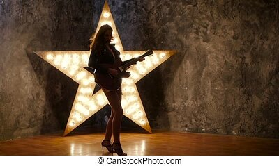 Female punk rock guitarist, dances shining star in the...