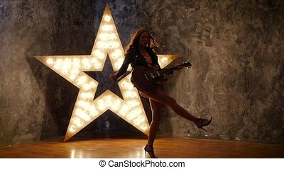 young rock guitarist, dances. shining star in the background. slow motion, silhouette