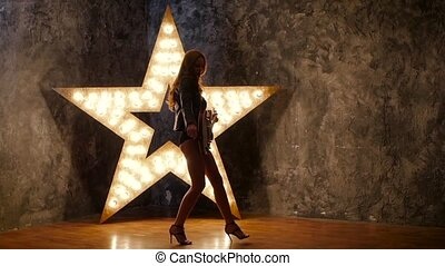 Sexy girl with electric guitar, shining star in the background. slow motion, silhouette