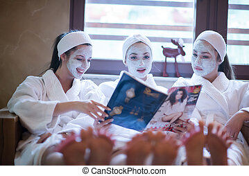 bachelorette party in spa, girls with face mask reading...