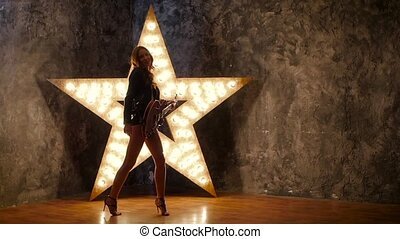 girl dancing and posing with electric guitar, shining star in the background. slow motion, silhouette