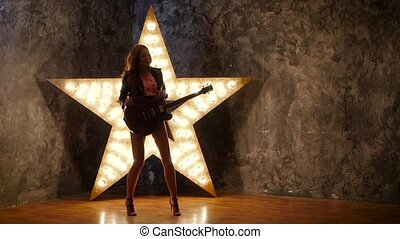 sexy girl dancing and posing with electric guitar, shining star in the background. slow motion, silhouette