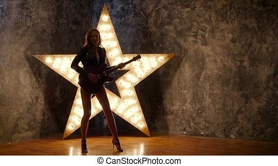 attractive rock girl playing the electric guitar, shining...