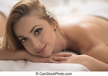 woman getting back massage in spa salon - beautiful young...