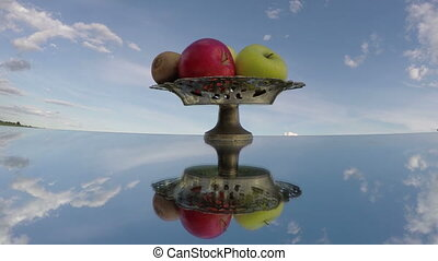 Green and red apples and kiwi placed in antique vase on...