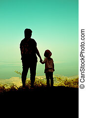 Silhouette back view of mother and daughter clasping hand...