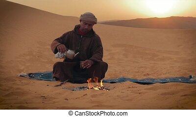 a tea in the desert - sahara man preparing a tea