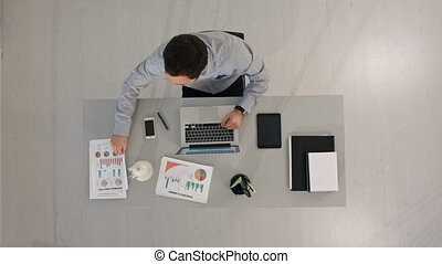 Top view of Businessman analyzing financial charts and...