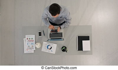 Top view of Businessman using a digital touch screen tablet and working at office desk
