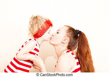 Happy mom and child girl kissing with love while looking at...
