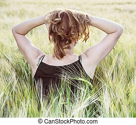 Young woman holds her hair by sunset in the field, rear view...