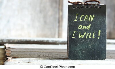 I can and I will, yellow lettering on a black plate.