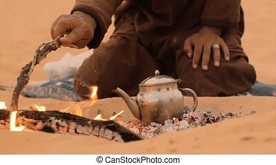 a tea in the desert, close up - sahara man preparing a tea