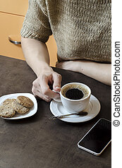 woman's hand holding a cup of coffee