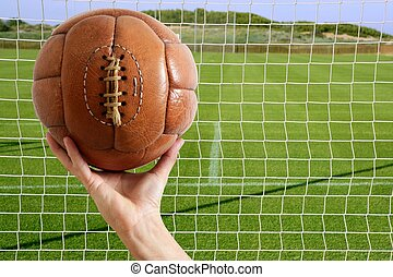 Football ball in hand net soccer goal