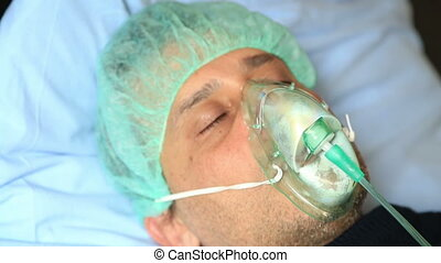 Man with oxygen mask - Diseased man wearing a oxygen mask in...