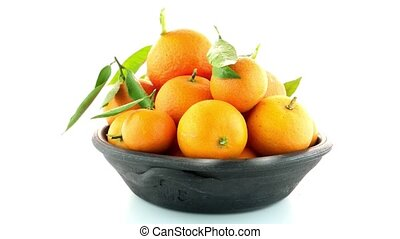 Tangerines on clay bowl isolated on white background