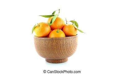 Tangerines on wooden bowl isolated on white background