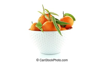 Tangerines on ceramic white bowl